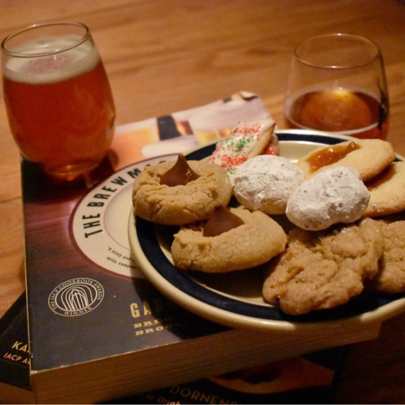 A photo of Christmas cookies (snowball cookies, apricot thumbprint cookies, orange gingerbread cookies, sugar cookies with buttercream frosting, and peanut butter blossom cookies) paired with craft beer.