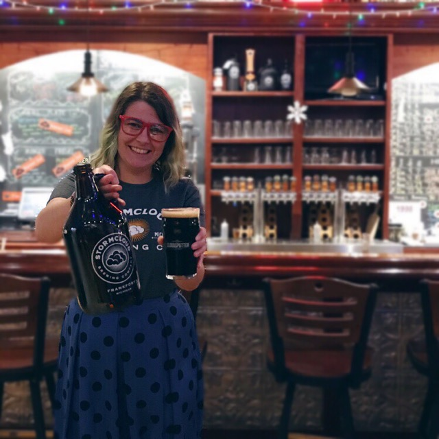 A photo of Amy from Polka Dots and Pints holding up a beer growler and a glass of beer at Stormcloud Brewing Co.
