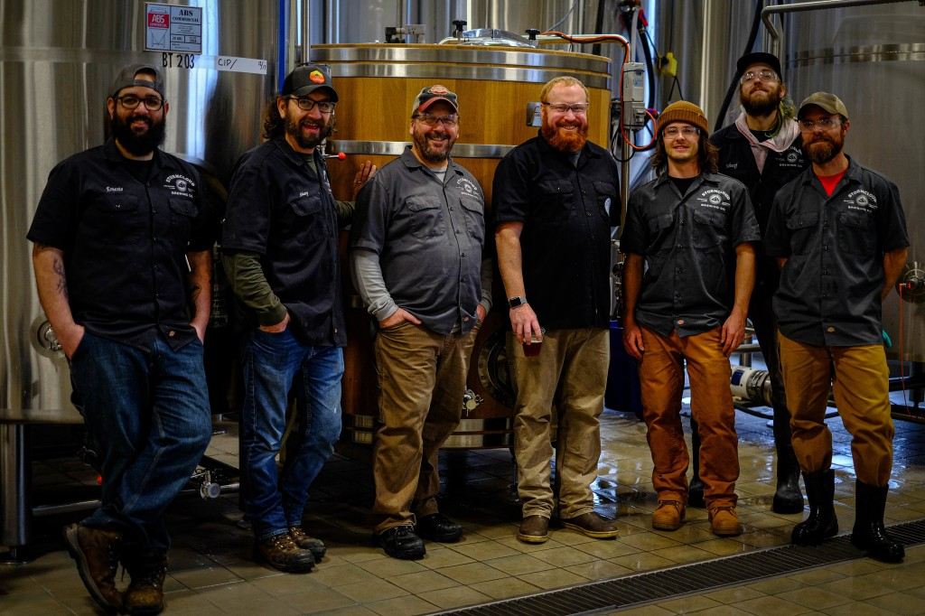 Brewers from Stormcloud Brewing Company and The Filling Station Microbrewery posing in front of 'The Collaborator' foeder.