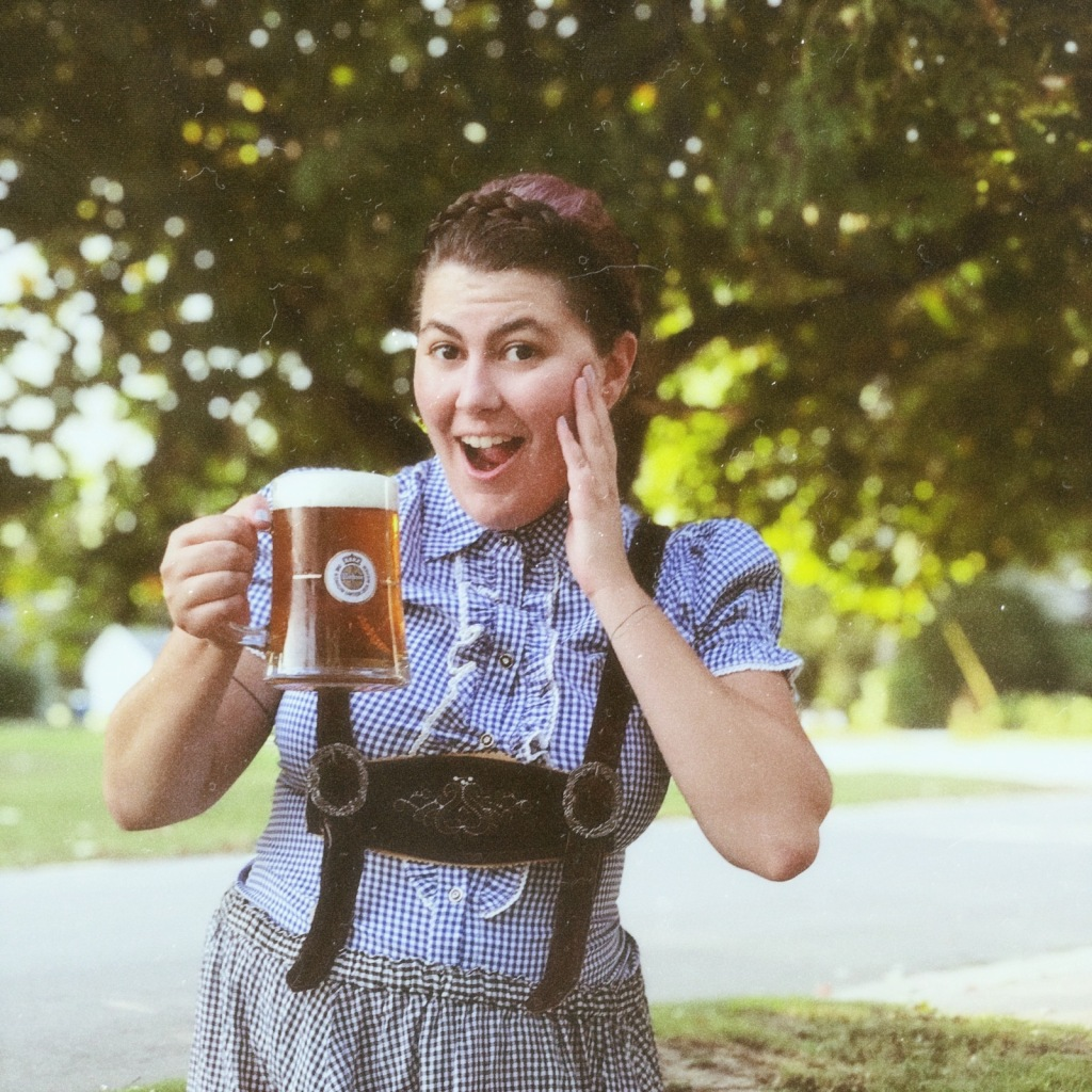 A photo of Amy wearing lederhosen holding a beer stein looking excited for Oktoberfest.